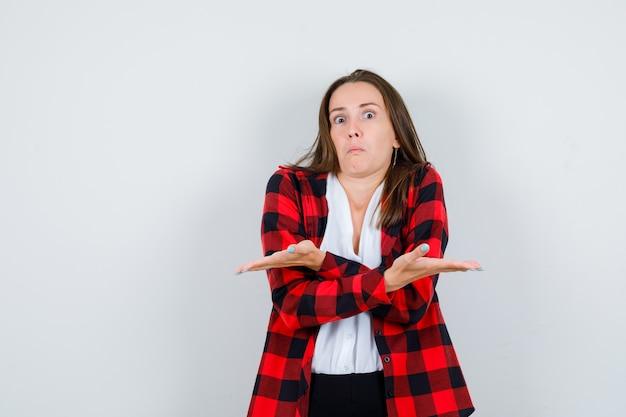 Portret młodej kobiety pokazujący bezradny gest w zwykłych ubraniach i patrzący na niezrozumiały widok z przodu