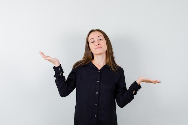 Portret młodej kobiety pokazujący bezradny gest