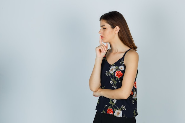Portret młodej kobiety pokazujący gest ciszy w bluzce i patrzący zamyślony widok z przodu