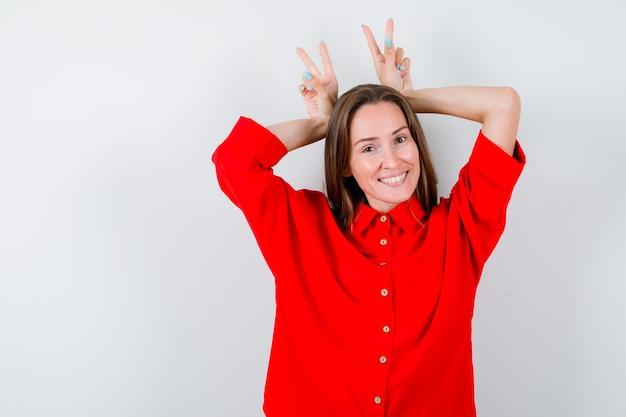 Portret młodej kobiety pokazujący gest uszy królika w czerwonej bluzce i patrzący szczęśliwy widok z przodu