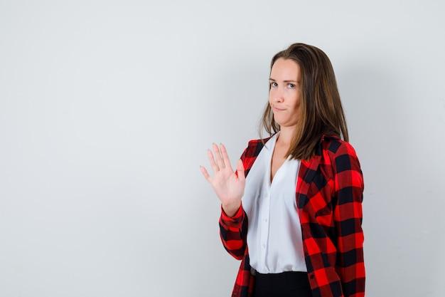 Portret młodej kobiety pokazujący gest zatrzymania w zwykłych ubraniach i patrzący na znudzony widok z przodu