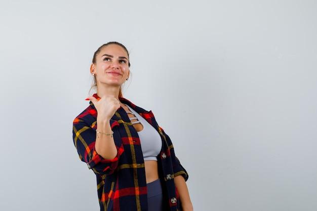 Portret młodej kobiety pokazujący kciuk w górę w górę, koszulę w kratkę, spodnie i cieszący się widok z przodu