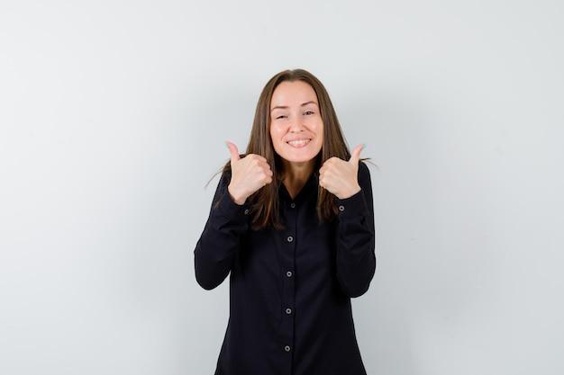 Portret młodej kobiety pokazujący podwójne kciuki w górę
