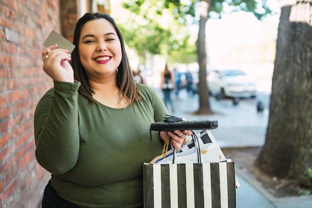 Portret młodej kobiety posiadającej kartę kredytową i torby na zakupy na zewnątrz na ulicy