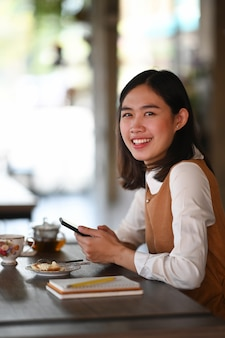 Portret młodej kobiety posiadania telefonu komórkowego i uśmiechnięte