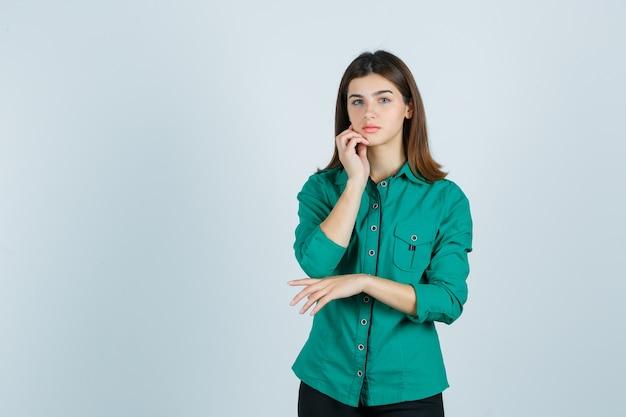 Portret młodej kobiety pozowanie, dotykając skóry na brodzie w zielonej koszuli i patrząc wdzięczny widok z przodu