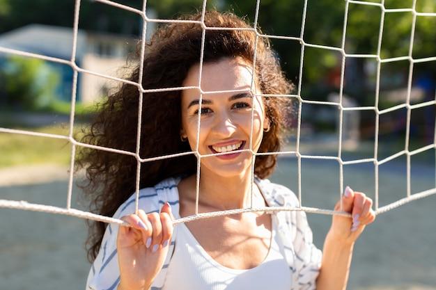 Portret młodej kobiety pozowanie obok boiska do siatkówki na zewnątrz