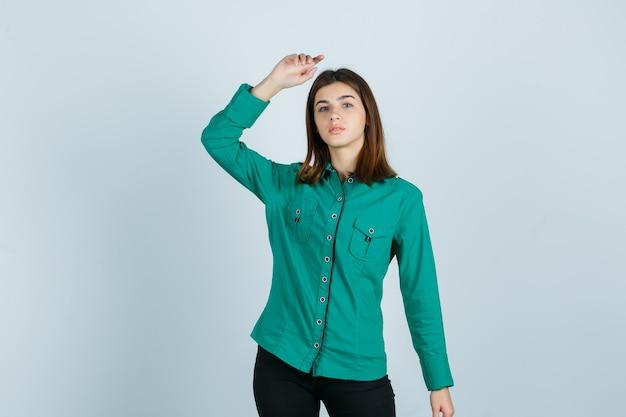 Portret młodej kobiety pozowanie, podnosząc rękę w zielonej koszuli i patrząc pewnie z przodu