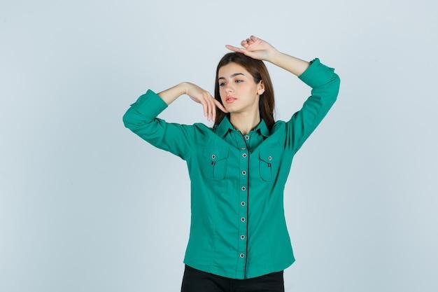 Portret młodej kobiety pozowanie z rękami wokół głowy w zielonej koszuli i patrząc delikatny widok z przodu