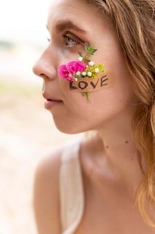 Portret młodej kobiety pozującej pewnie na zewnątrz z kwiatami