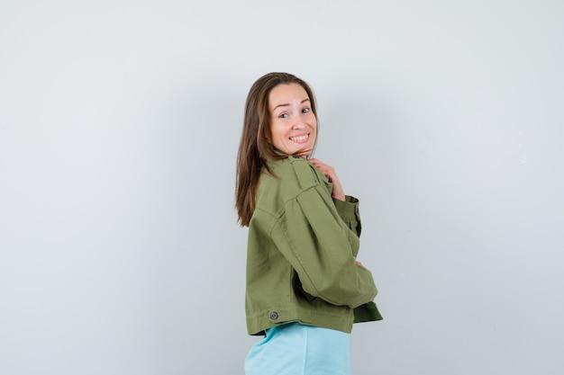 Portret młodej kobiety pozuje patrząc na kamerę przez ramię w zielonej kurtce i patrząc wesoło