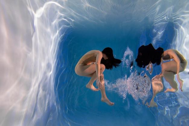 Portret młodej kobiety pozuje zanurzony pod wodą