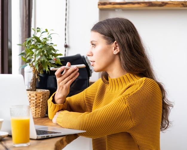 Portret młodej kobiety pozytywne nagrywanie wiadomości audio, mówiąc do mikrofonu telefonu komórkowego