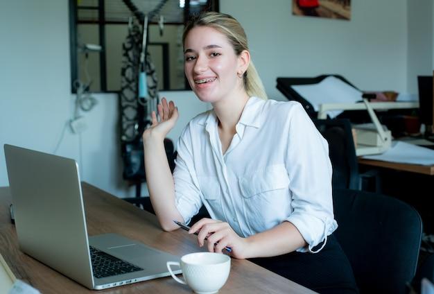 Portret młodej kobiety pracownik biurowy siedzi na biurko przy użyciu komputera przenośnego patrząc na kamery uśmiechnięty radośnie pracy w biurze