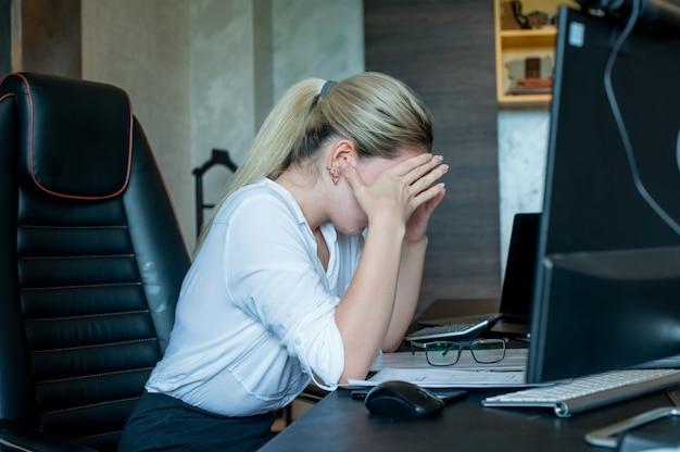 Portret młodej kobiety pracownik biurowy siedzi na biurko z dokumentów przy użyciu komputera, patrząc zmęczony i znudzony o ból głowy pracujący w biurze