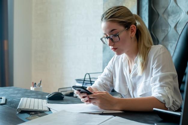 Portret młodej kobiety pracownik biurowy siedzi przy biurku z dokumentów posiadających smartfon patrząc na ekran z poważnym wyrazem twarzy pracującej w biurze