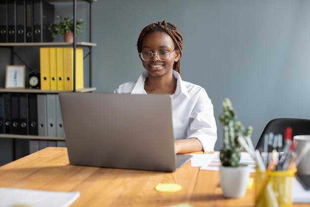 Portret młodej kobiety pracującej na swoim laptopie w firmie rozpoczynającej działalność