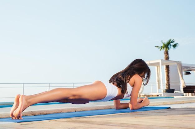Portret młodej kobiety pracującej na zewnątrz na matę do jogi
