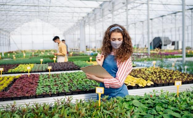 Portret młodej kobiety pracującej w szklarni w centrum ogrodniczym, koncepcja koronawirusa.