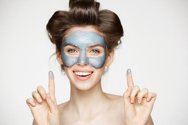Portret młodej kobiety przetargu w lokówki i maseczka na twarz z uśmiechem. koncepcja pielęgnacji skóry i urody.