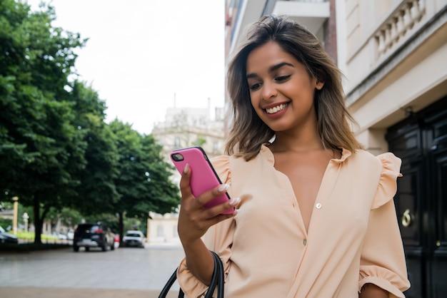 Portret młodej kobiety przy użyciu swojego telefonu komórkowego podczas spaceru na ulicy