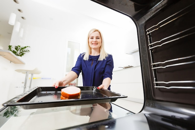 Portret młodej kobiety przygotowującej jedzenie w kuchni. młoda gospodyni trzyma świeżo upieczone mięso