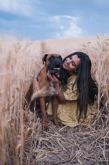Portret młodej kobiety przytulający psa na środku pola pszenicy. koncepcja przyrody i zwierząt