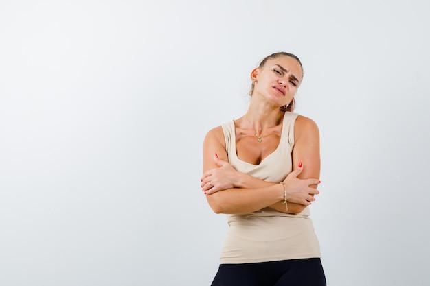 Portret młodej kobiety przytulanie się w beżowym podkoszulku bez rękawów i patrząc zmęczony widok z przodu