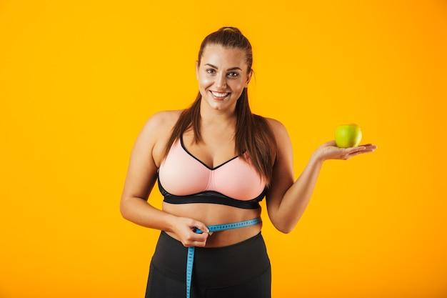 Portret młodej kobiety pulchne w stanik sportowy pomiaru jej talii miernikiem i trzymając jabłko, odizolowane na żółtym tle