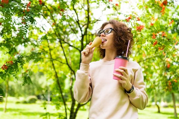 Portret młodej kobiety rasy białej o zielonych oczach, doskonałym uśmiechu, pulchnych ustach, okularach chodzi w naturze i pije kawę lub koktajl i je lody