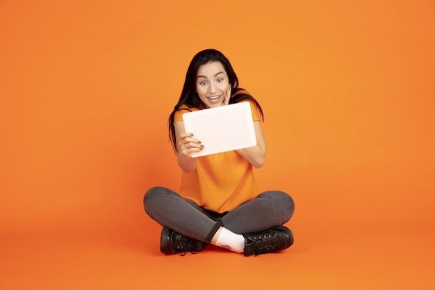 Portret młodej kobiety rasy kaukaskiej na pomarańczowym tle studio. piękna brunetka modelka w koszuli. pojęcie ludzkich emocji, wyraz twarzy, sprzedaż, reklama. copyspace. korzystanie z tabletu, vlogowanie.