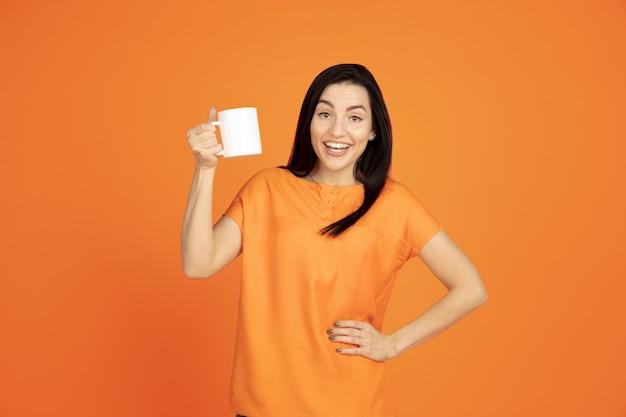 Portret młodej kobiety rasy kaukaskiej na pomarańczowym tle studio. piękna brunetka modelka w koszuli. pojęcie ludzkich emocji, wyraz twarzy, sprzedaż, reklama. copyspace. picie kawy lub herbaty.