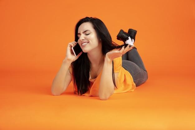 Portret młodej kobiety rasy kaukaskiej na pomarańczowym tle studio. piękna brunetka modelka w koszuli. pojęcie ludzkich emocji, wyraz twarzy, sprzedaż, reklama. copyspace. rozmawiam przez telefon.