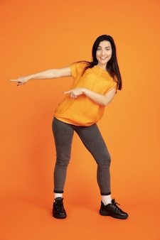 Portret młodej kobiety rasy kaukaskiej na pomarańczowym tle studio. piękna brunetka modelka w koszuli. pojęcie ludzkich emocji, wyraz twarzy, sprzedaż, reklama. copyspace. wskazując, pokazując.