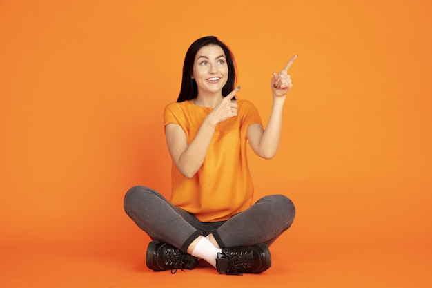 Portret młodej kobiety rasy kaukaskiej na pomarańczowym tle studio. piękna brunetka modelka w koszuli. pojęcie ludzkich emocji, wyraz twarzy, sprzedaż, reklama. copyspace. wskazując w górę.