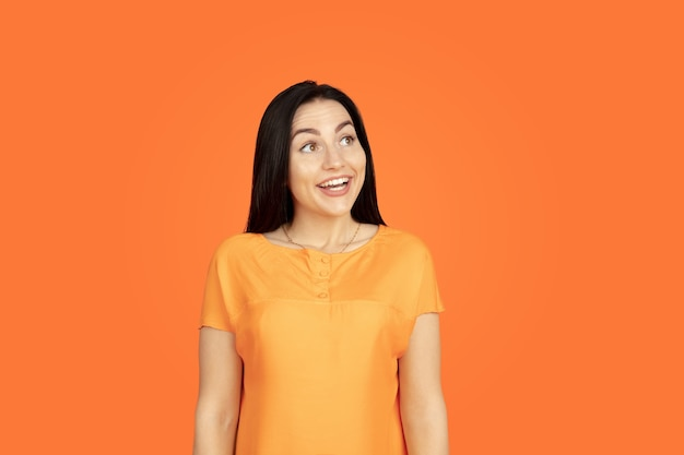 Portret młodej kobiety rasy kaukaskiej na pomarańczowym tle studio. piękna brunetka modelka w koszuli. pojęcie ludzkich emocji, wyraz twarzy, sprzedaż, reklama. copyspace. wygląda marzycielsko, uśmiecha się.
