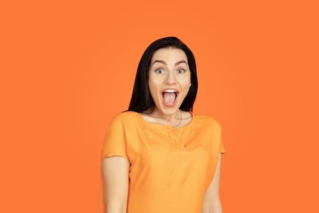 Portret młodej kobiety rasy kaukaskiej na pomarańczowym tle studio. piękna brunetka modelka w koszuli. pojęcie ludzkich emocji, wyraz twarzy, sprzedaż, reklama. copyspace. zszokowany, zdumiony.
