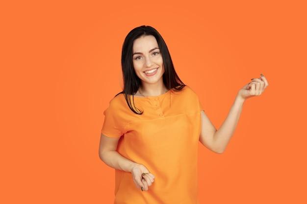 Portret młodej kobiety rasy kaukaskiej na pomarańczowym tle studio.