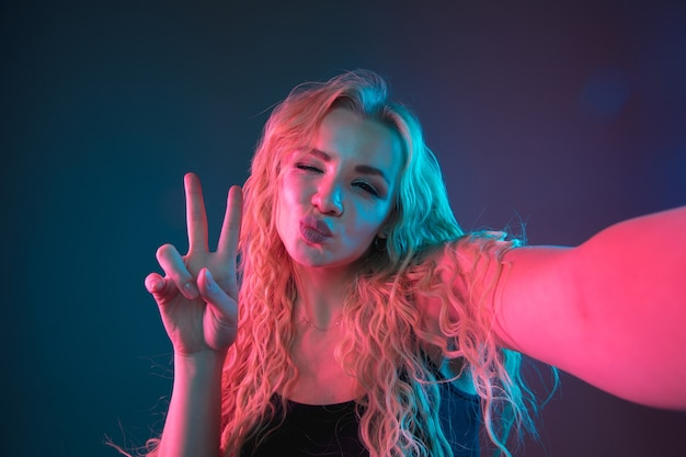 Portret młodej kobiety rasy kaukaskiej na tle gradientu w świetle neonu. piękna modelka o niezwykłym wyglądzie. pojęcie ludzkich emocji, wyraz twarzy, sprzedaż, reklama. robienie selfie, pozowanie.