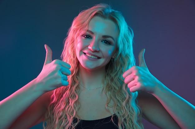 Portret młodej kobiety rasy kaukaskiej na tle gradientu w świetle neonu. piękna modelka o niezwykłym wyglądzie. pojęcie ludzkich emocji, wyraz twarzy, sprzedaż, reklama. wskazując, uśmiechając się. copyspace.