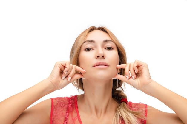 Portret młodej kobiety rasy kaukaskiej o średnio jasnych włosach zaplecionych w kucyk, z piękną, czystą skórą, wykonuje ćwiczenia przeciwzmarszczkowe