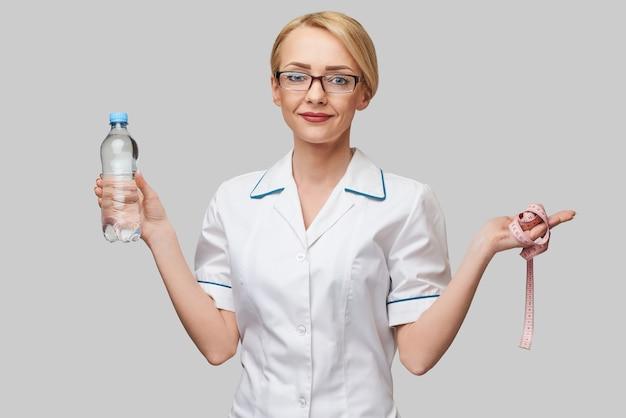 Portret młodej kobiety rasy kaukaskiej służby zdrowia trzymając butelkę wody i miarkę stojącą nad jasnoszarą ścianą