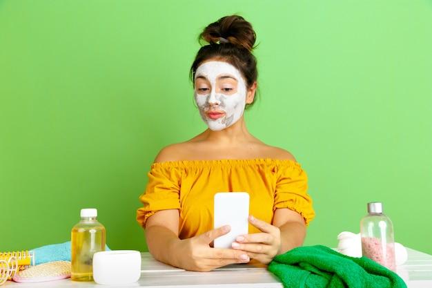 Portret młodej kobiety rasy kaukaskiej w rutynowej pielęgnacji skóry i włosów dzień piękna. modelka z naturalnymi kosmetykami robi selfie podczas nakładania maseczki na twarz. pielęgnacja ciała i twarzy, koncepcja naturalnego piękna.