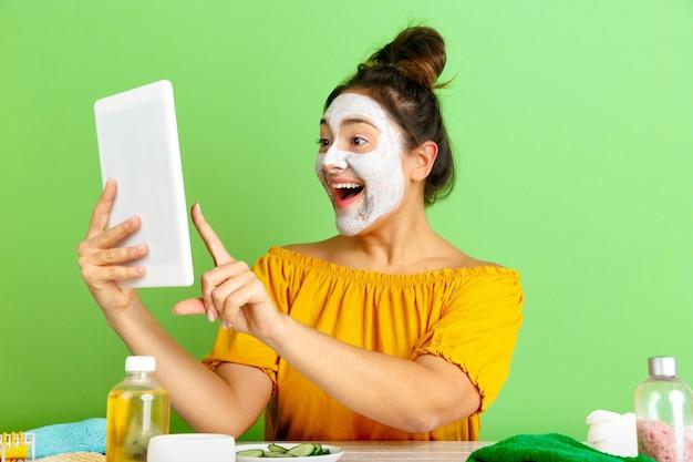 Portret młodej kobiety rasy kaukaskiej w rutynowej pielęgnacji skóry i włosów dzień uroda. modelka robi selfie, vlog lub wideokonferencję podczas nakładania maseczki na twarz. koncepcja selfcare, naturalne piękno i kosmetyki.