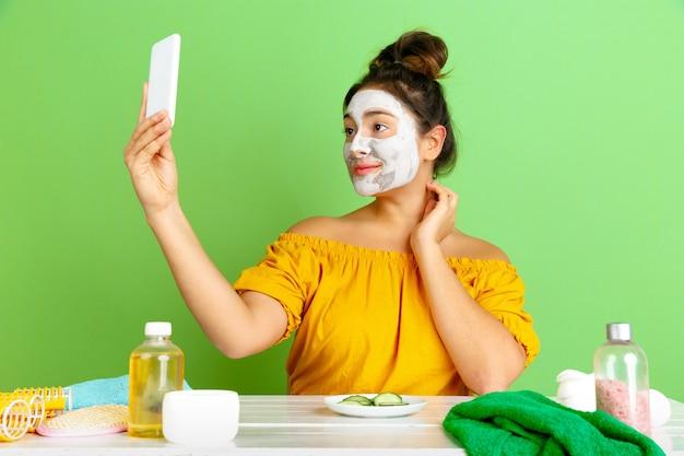 Portret młodej kobiety rasy kaukaskiej w rutynowej pielęgnacji skóry i włosów dzień uroda. modelka z naturalnymi kosmetykami robi selfie podczas nakładania maseczki na twarz. pielęgnacja ciała i twarzy, koncepcja naturalnego piękna.