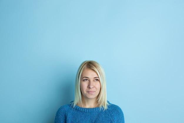 Portret młodej kobiety rasy kaukaskiej wygląda marzycielsko, słodko i szczęśliwie. myślenie, zastanawianie się, śnienie na niebieskiej przestrzeni