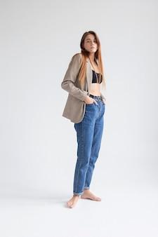 Portret młodej kobiety rasy kaukaskiej z długimi włosami w czarny top, niebieskie dżinsy i marynarkę na tle białego studia z rękami w kieszeniach. ładna dziewczyna pozuje z bosymi stopami