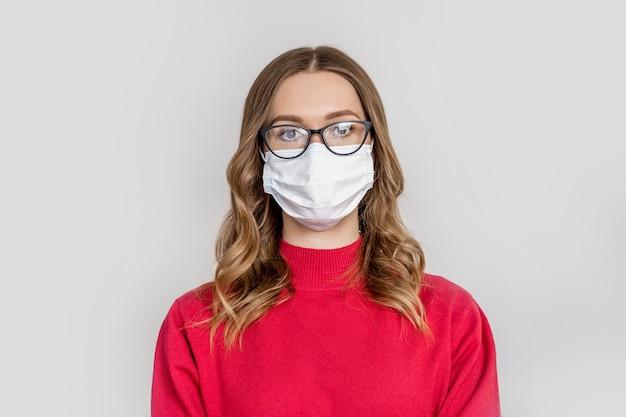 Portret młodej kobiety rasy kaukaskiej z medyczną maską oddechową, czarnymi okularami i czerwonym świątecznym swetrem na białym tle na szarym tle studia