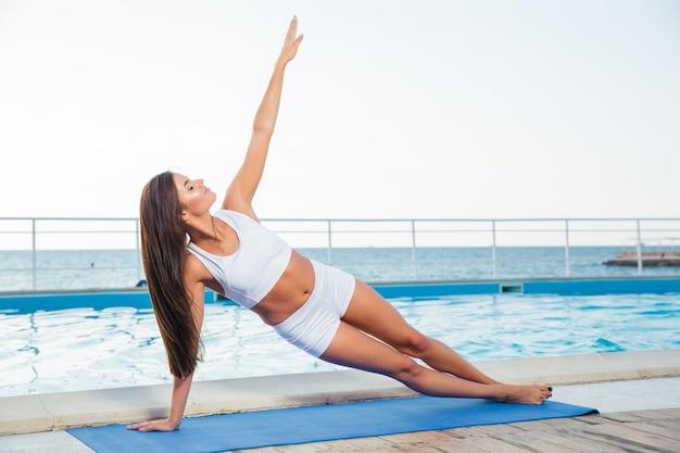 Portret młodej kobiety robi ćwiczenia jogi na świeżym powietrzu