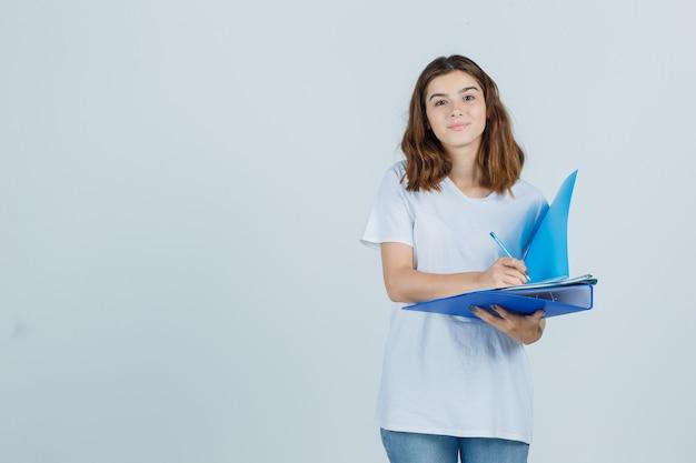 Portret młodej kobiety robienie notatek na folderze w biały t-shirt, dżinsy i wesoły widok z przodu